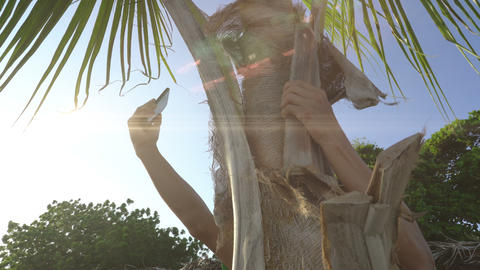 Man sitting on palm tree trying to get connection on his mobile phone, searching Footage