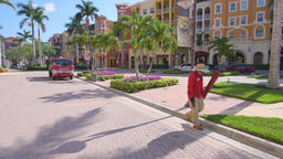 Naples, Florida Bayfront community landscaping worker walking by buildings Footage