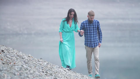 young couple walking along the shore of the pond on a date. Young man with a Footage