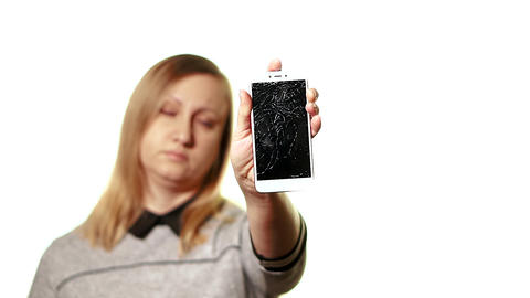 The concept of a broken gadget. Frustrated and tired middle-aged woman holding a Live Action