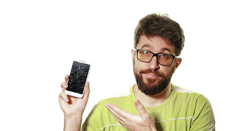 The concept of a broken gadget. Bearded frustrated man shows the smartphone with Live Action