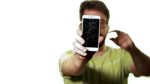 The concept of a broken gadget. A man shows the smartphone with a broken screen Live Action