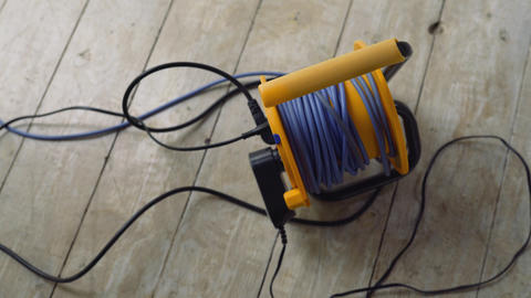 Wires plugged to the electric extension cable, wires on the floor, electrical Live Action