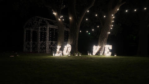 Wooden letters with bulb lights. Word - Love. Illuminated word LOVE on the stage Live Action