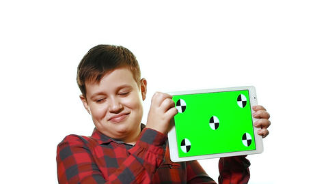 Cheerful boy holding a tablet in his hand with a green screen Footage