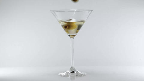 Martini cocktail with an olive - classic drink Live Action