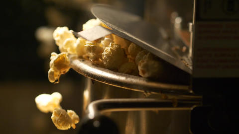 Fresh roasted pop corn pop out of the bowl - pop corn maker in a movie theater Live Action