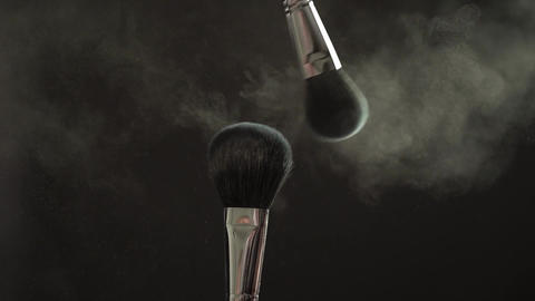 Two makeup brushes with powder on a dark background, slow motion Footage