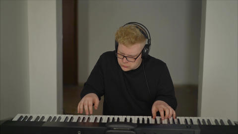 A composer with headphones playing the digital piano. Musician playing Live Action