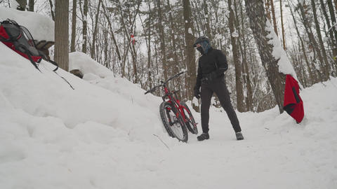 The cyclist prepares to descend from a snowy mountain. The cyclist is preparing Footage