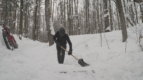 Cyclist cleans his springboard with a shovel in the winter. Man cleans a shovel Live Action