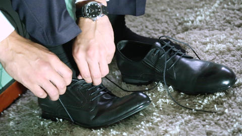 Young man tying shoelace on sport shoes indoors, closeup Live Action