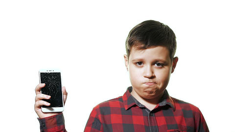 The concept of a broken gadget. Sad teen boy on white background Live Action