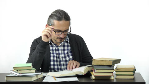 man sitting at table studying hard Footage