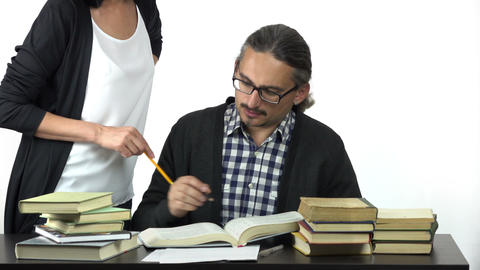 man sitting at table studying hard, discussing with woman how to solve the task Footage