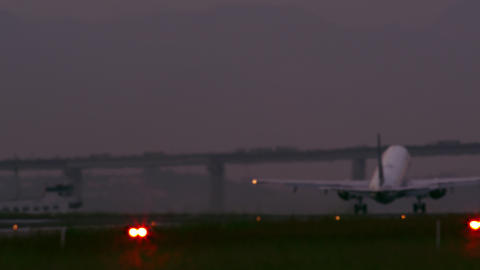 Commercial airplane taking off at Jacarepaguá airport with bridge in the backgr Footage