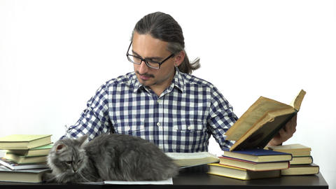 man sitting at table studying and writing in notebook. his cats are looking at h Footage