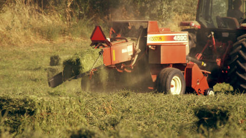 Shot of a farmer operating a hay baler as he goes around the field Footage