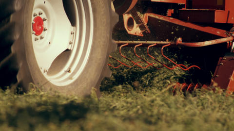 Close-up shot of the bottom of a hay baler as it gathers hay from the ground Footage