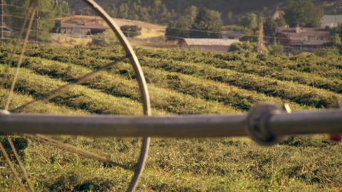 Static shot of farm as seen from behind a water pipe and wheel Footage