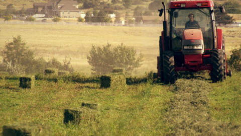 Static shot of farmer gathering hay using tractor Footage