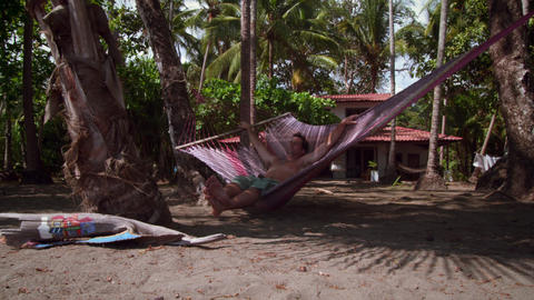 Dolly shot of a man enjoying himself on a hammock Footage