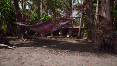 Tracking footage of an empty hammock and a house Footage