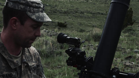 Slow motion shot of soldier setting up mortar launcher and instructor inspecting Footage