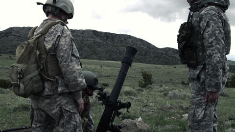 Slow motion shot of soldiers adjusting mortar launcher at range Footage