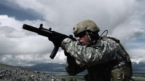 Close up of a soldier with sub-machine gun down, aiming, firing, and lowering we Footage