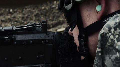 Close-up of a soldier aiming a belt-fed machine gun and firing Footage