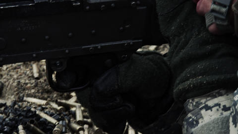Close-up moving from a soldier's face to his hand pulling the trigger Footage