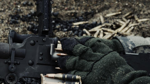 Close-up of gloved hands loading a chain of rounds Footage