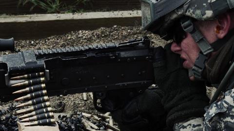 Close-up of a soldier's firing a belt-fed machine gun Footage