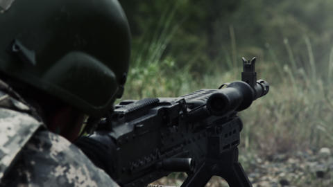 Close view over the shoulder of a soldier as he shoots a belt-fed machine gun Footage