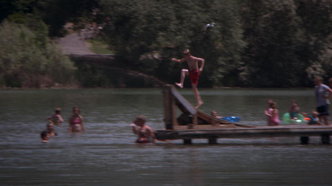 Slow motion, panning shot of kid jumping off the end of a dock into a lake Footage