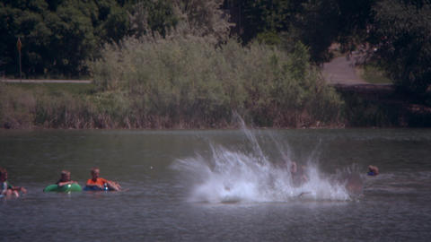 Slow motion, panning shot of kid jumping his bike and spinning into a lake Footage