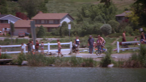 Slow motion, panning shot of a boy riding his bike off a ramp into a lake Footage