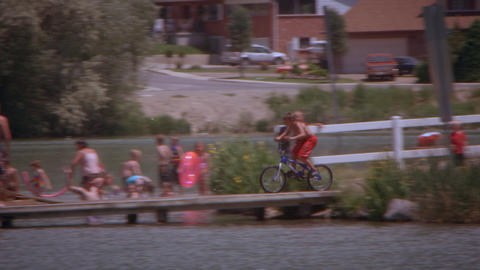Slow motion, panning shot of a kid riding his bike into a lake Footage