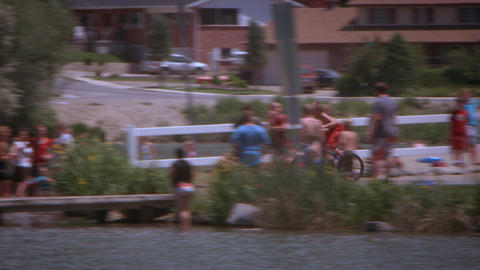 Panning, slow motion shot of a boy riding his bike off a dock and into a lake Footage