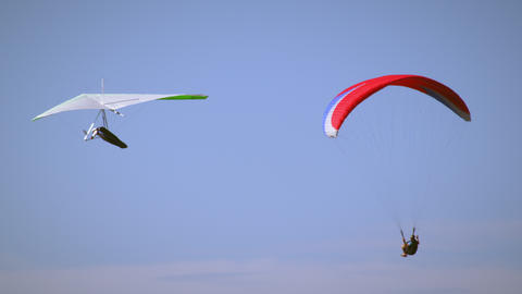 A paraglider and hang glider are flying in the same direction close to eachother Footage