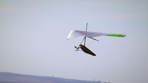 Hang glider soaring through air with valley and mountains seen in distance Footage