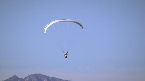 Paraglider is soaring through the air, soon joined by hang glider Footage