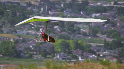 Shot of hang glider flying near mountain edge as another glider waits to take of Footage