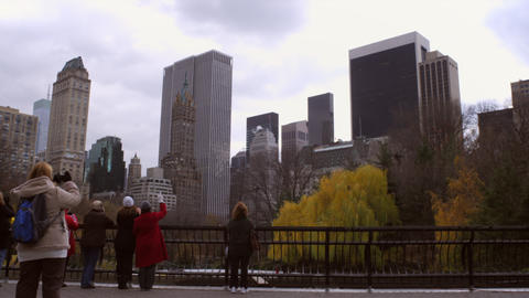 Shot of tourists taking pictures of cityscape and ice rink Footage