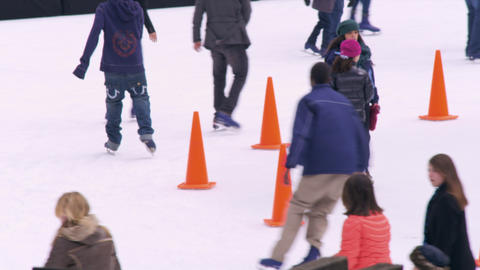 Slow motion panning shot of ice skaters on the Central Park ice rink Footage