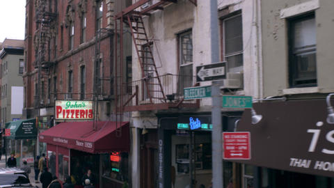 Dolly shot of small businesses on a street in New York City Footage