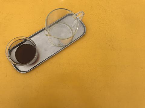 glass cup of coffee and handle container beaker with aluminum saucer on yellow table Photo