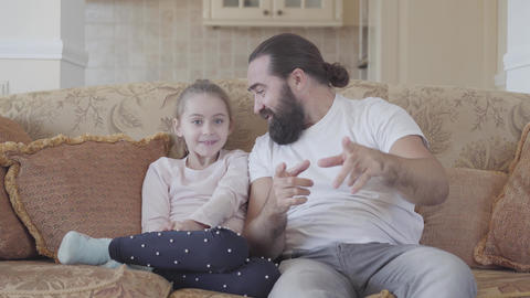 Cute small daughter with her funny father watching interesting film on tv with Footage