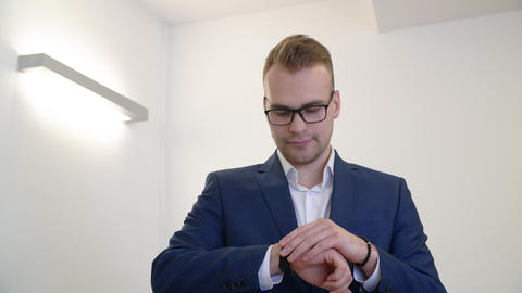 Young confident businessman in glasses checking the time GIF